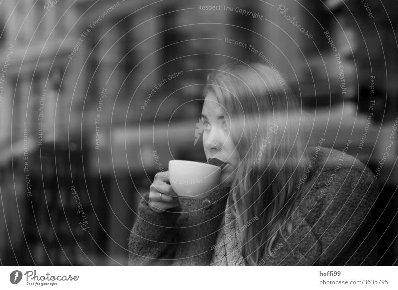 die junge Frau trinkt Kaffee und blickt durch die Scheibe auf die andere Strassenseite Kaffeetrinken Frauengesicht Junge Frau straßenkaffee