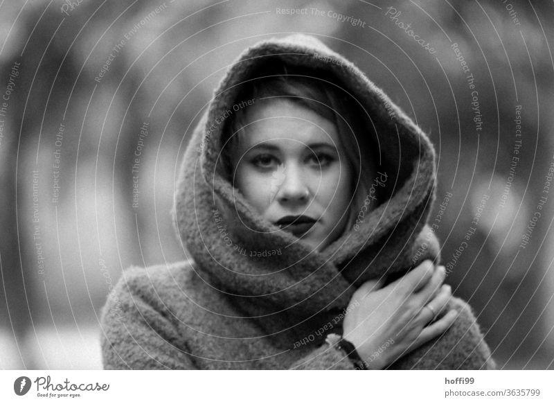 Die junge Frau im Mantel mit Kapuze schaut in die Kamera Porträt Junge Frau Frauengesicht unscharfer Hintergrund 18-30 Jahre Erwachsene portraite Mensch feminin