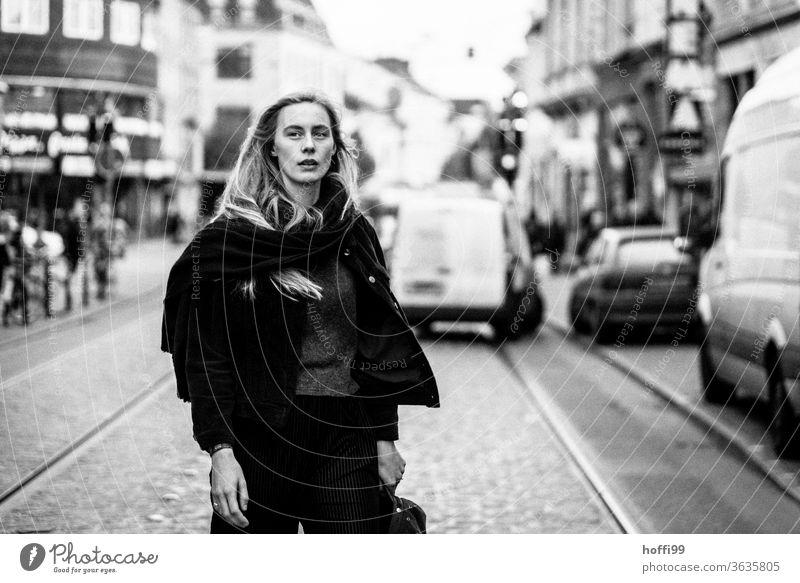 die Frau quert die Strasse und blickt skeptisch ob dem da kommenden ... feminin Kopf Frauengesicht Junge Frau 18-30 Jahre nachdenklich blond Erwachsene