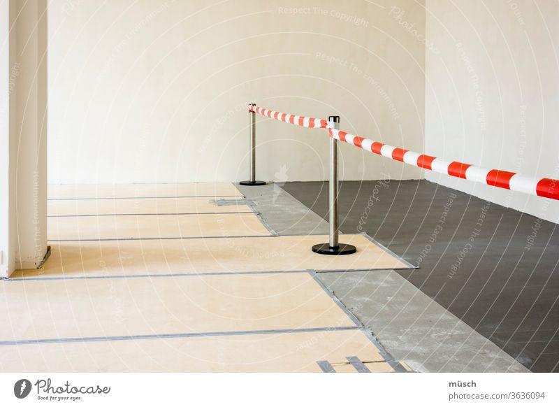 rot-weißes Abstandsband im Raum Absperrband Säule schwarz Wand hell Absperrung Band Bauarbeiten Renovierung Weg Erlaubnis Verbot Markierung Fußboden Platten