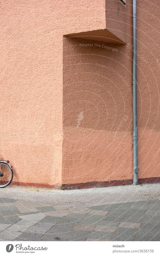 Hausecke mit Fahrrad und Abflußrohr Ecke Rohr Platten rosa grau braun Dreieck Farbe Leere Frage Schattierung Unterstand kleiner Balkon Muster Fußweg