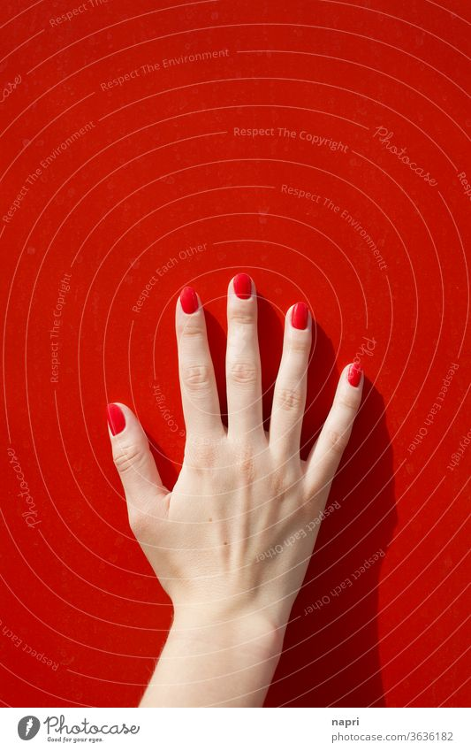 Signalwirkung | Frauenhand mit rot lackierten Fingernägeln auf roter Wand. Hand Junge Frau Nagellack weiblich schön berühren feminin gepflegt abstützen