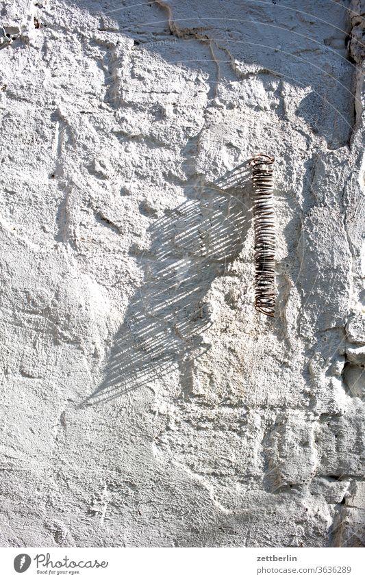 Sprungfeder mit Schatten licht mauer mauerwerk schatten sonne sprungfeder wand fuge putz spirale