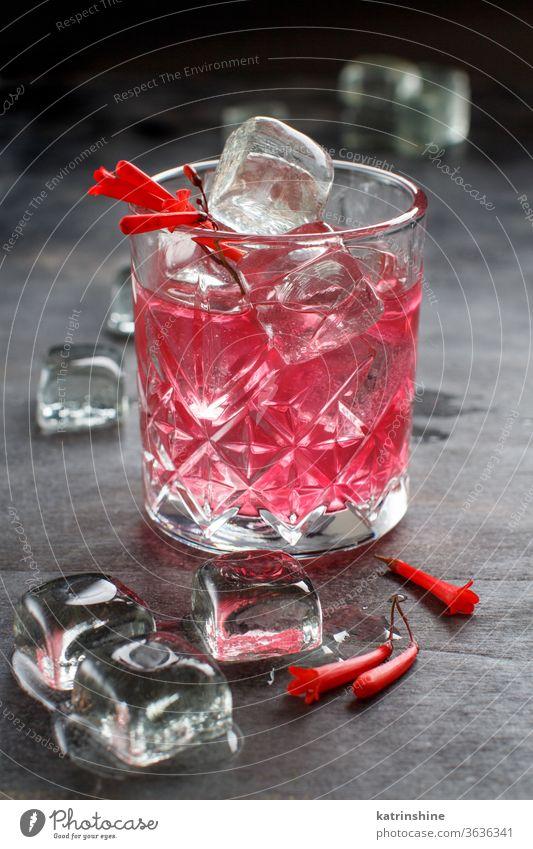 Kosmopolitischer Cocktail in einem mit rosa Blumen dekorierten Glas Kirsche weltoffen Barkeeper Eis grau Werkzeuge Stahl Alkohol Sommer erfrischend Party