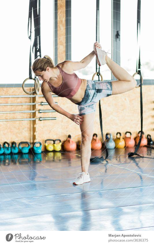 Junge sportliche Frau, die im Fitnessstudio die Beine streckt aktiv Aktivität Erwachsener Aerobic Athlet attraktiv schön blond Körper Kaukasier Energie Übung