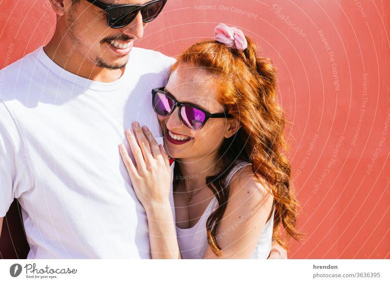 junges Paar umarmt sich und lächelt auf rotem Hintergrund Lächeln Liebe Menschen Glück Zusammensein männlich Frau Fröhlichkeit umarmend Freund Umarmung