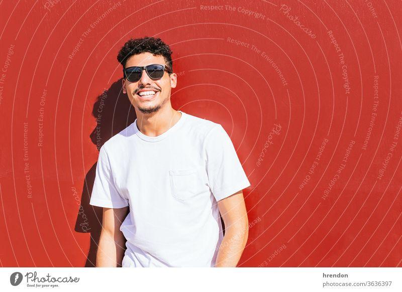 Porträt eines jungen Mannes mit Sonnenbrille, der auf einer roten Wand lächelt Lächeln männlich Typ Lifestyle Glück attraktiv Fröhlichkeit posierend Stil