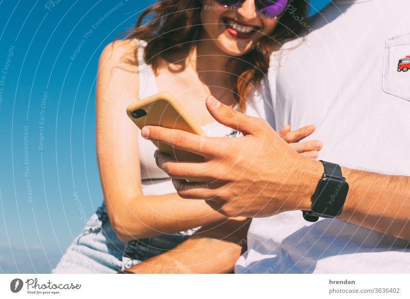 glückliches junges Paar, das auf sein Smartphone schaut und lächelt Lächeln Himmel Frau Technik & Technologie Zusammensein Beteiligung Blick Lifestyle Freund