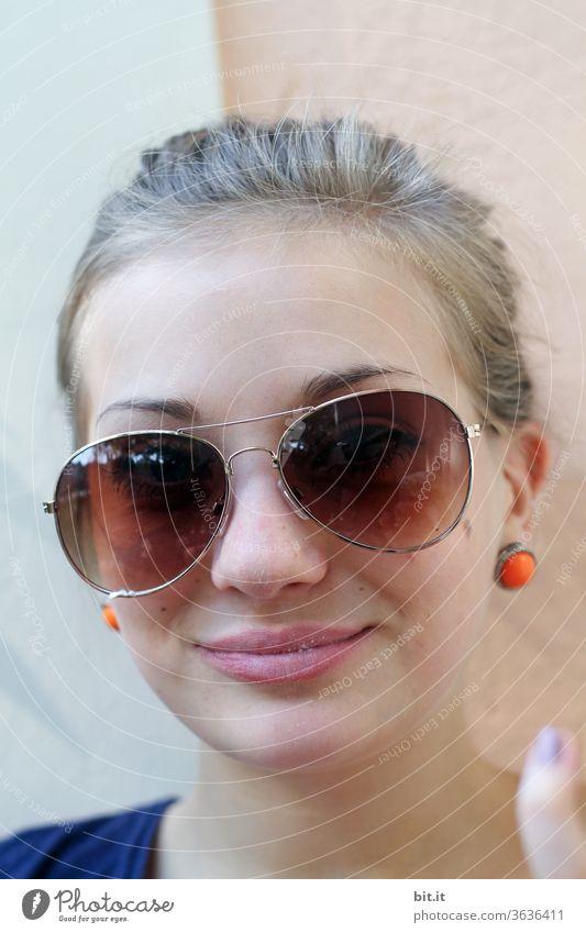 Teenager vor einer mediteranen Wand mit orangen Ohrringen, Pferdeschwanz und Sonnenbrille. Jugendliche mit blonden Haaren lächelt in die Kamera. Urlaubsfoto einer jungen Frau im Sommer, vor heller Fassade, Mauer. Sonnenschutz durch schiefe Sonnenbrille.