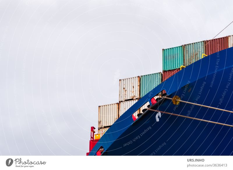 bunte Container auf einem riesigen Containerschiff bei bedecktem Himmel | Detailaufnahme Ozeanriese Güterverkehr & Logistik blau rot bewölkter Himmel Fracht