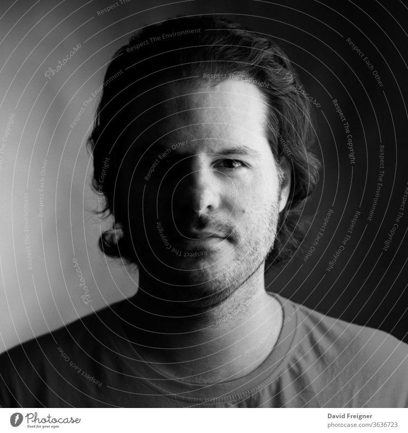 Porträt eines Mannes, aufgenommen auf analogem Mittelformatfilm. Analoge Filmfotografie und Kornkonzept. jung Gesicht gutaussehend schwarz weiß Typ Person