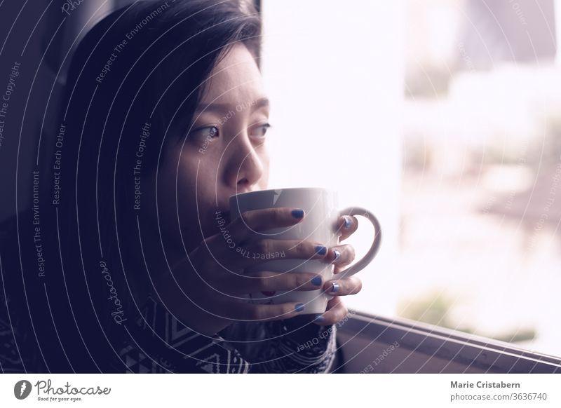 Asiatisches Mädchen, das an einem frühen Herbstmorgen am Fenster Kaffee trinkt, zeigt das Konzept der neuen normalen, häuslichen Quarantäne und Selbstisolierung während der Covid-19-Pandemie