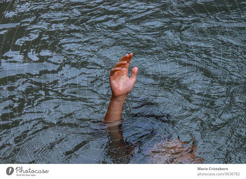 Eine Hand, die aus dem Wasser ragt, um das Konzept des Ertrinkens, der Krise der psychischen Gesundheit, der Depression und des Kampfes zu zeigen