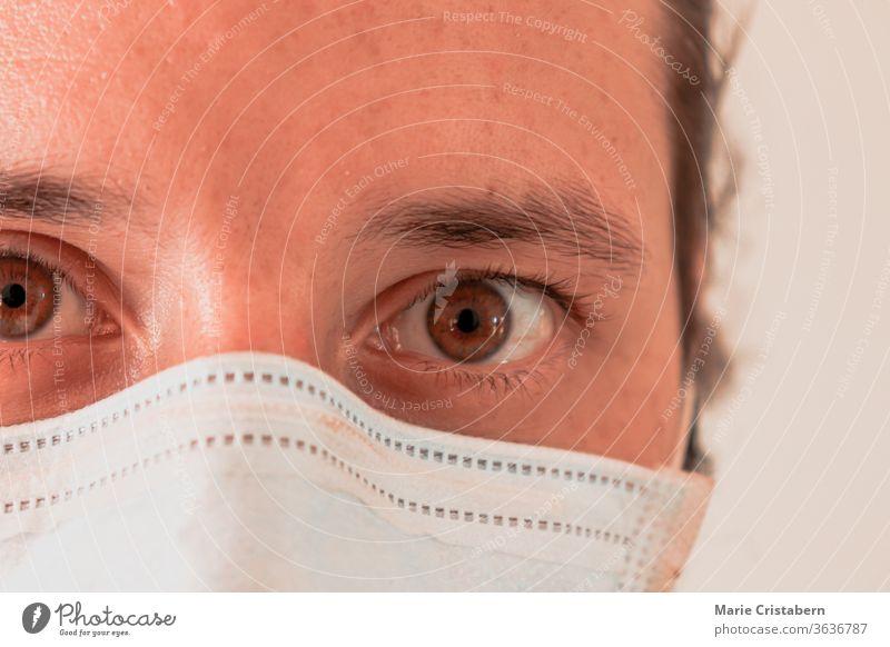 Nahaufnahme eines überarbeiteten Krankenpflegers mit einer chirurgischen Maske Kaukasisch männlich Augen weit geöffnet Operationsmaske covid-19-Pandemie