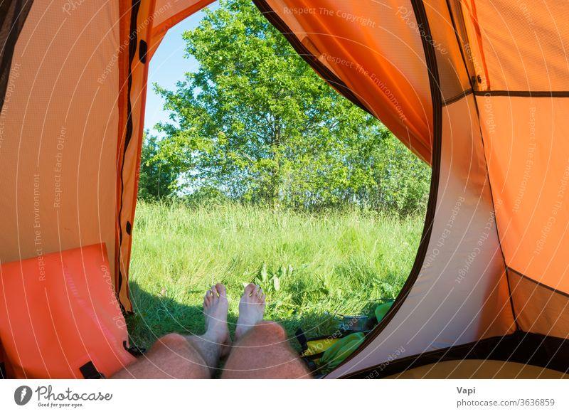 Mann ruht sich im orangefarbenen Zelt aus Lager Urlaub Camping Beine Natur im Inneren Ansicht Gras Fuß Menschen ruhen Erholung Wald Baum Landschaft Abenteuer