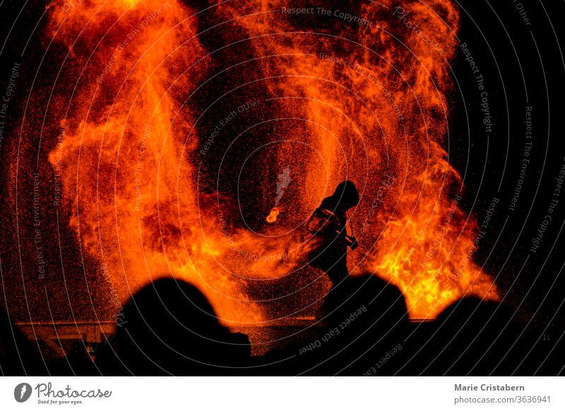Silhouette eines Feuerwehrmannes, der vor den Blicken einer Menschenmenge kämpft, um ein tobendes Feuer einzudämmen Leben retten wesentlicher Arbeiter