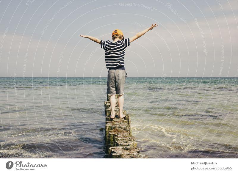 Junge balanciert auf Holzpollern an der Ostsee sommer shirt t-shirt streifen lebensfreude küste urlaub ferien balancieren brandung wellen wasser meer