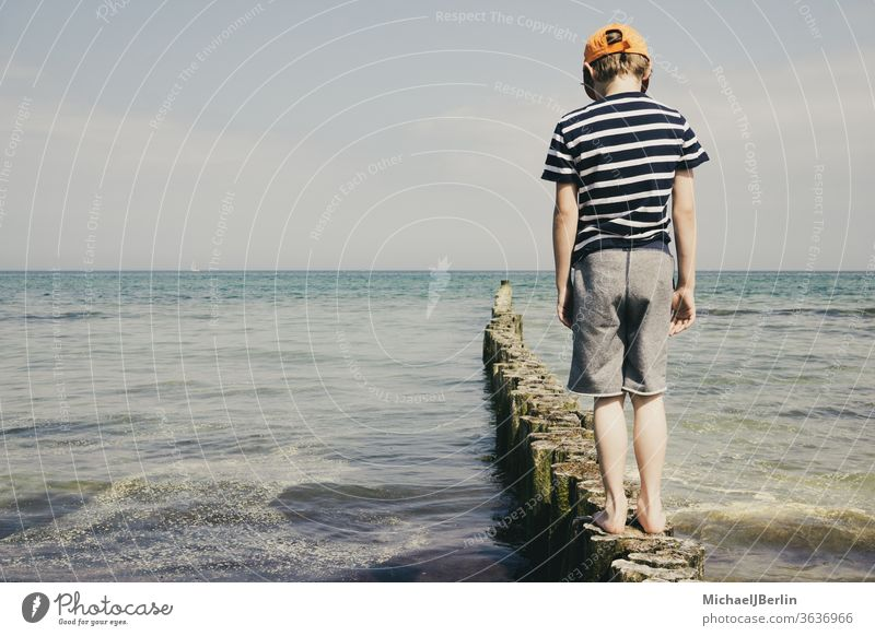 Junge an der Ostsee steht auf Pollern MEER Schuljunge Kind Kinder Feiertage Urlaub Osten Deutschland Rostock Warnemünde Meinungsforscher Gleichgewicht Freude