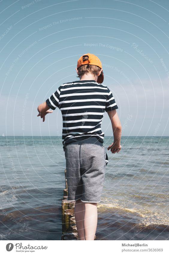Junge balanciert auf Pollern in der Ostsee junge kind schuljunge eine person kinder balance spaß meer wasser wellen poller brandung küste urlaub ferien sommer