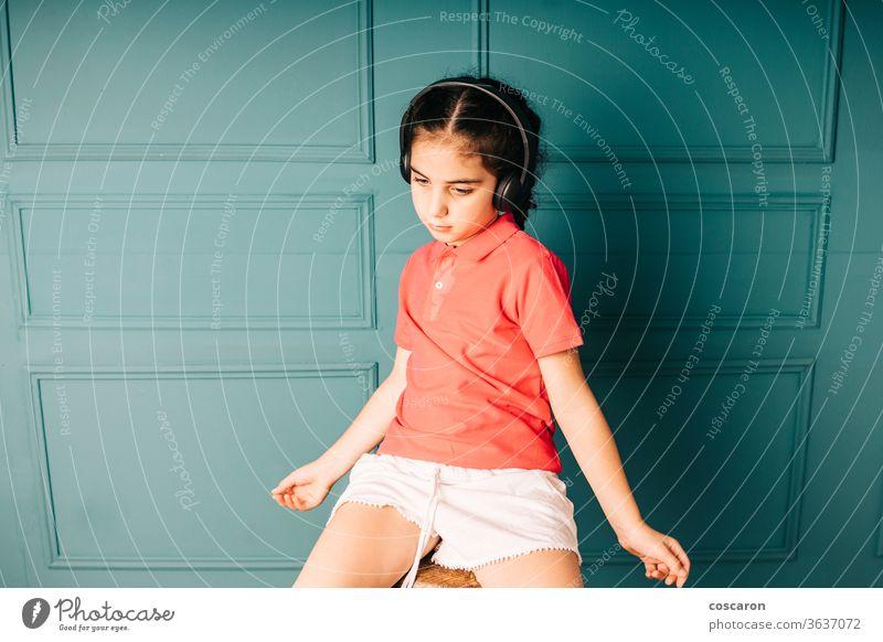 Süßes Mädchen hört Musik mit Kopfhörern bezaubernd allein attraktiv Hintergrund schön blau sorgenfrei lässig heiter Kind Kindheit Farbe niedlich Tanzen genießen