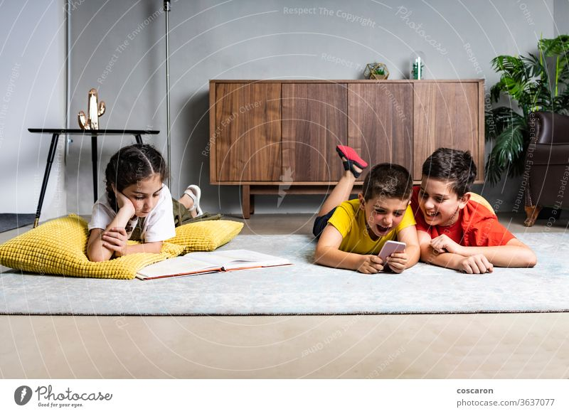Kleines Mädchen liest ein Buch, während zwei Jungen mit einem Smartphone spielen Brüder Handy heiter Kind Kindheit Kinder Mitteilung niedlich Daten anders