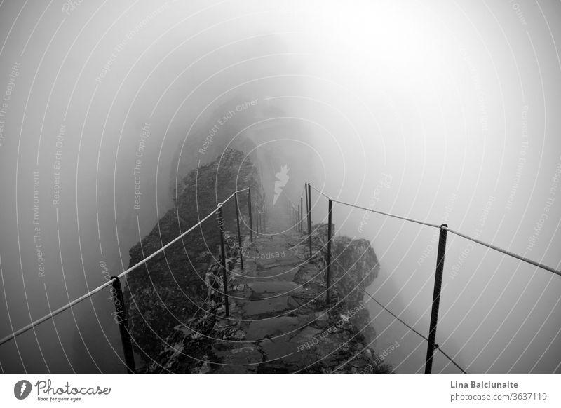 Schwarzweißfoto des Weges zu den Berggipfeln Pico Ruivo und Pico do Areeiro im Nebel auf Madeira, Portugal. Ein mystischer Pfad, Weg ins Nirgendwo oben