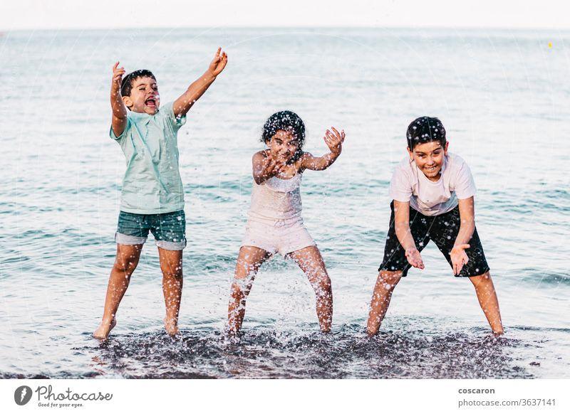 Drei Kinder spielen am Strand mit dem Wasser Aktion aktiv schön blau Junge hell heiter Konzept Tropfen genießen frisch Spaß lustig Mädchen Fröhlichkeit Glück