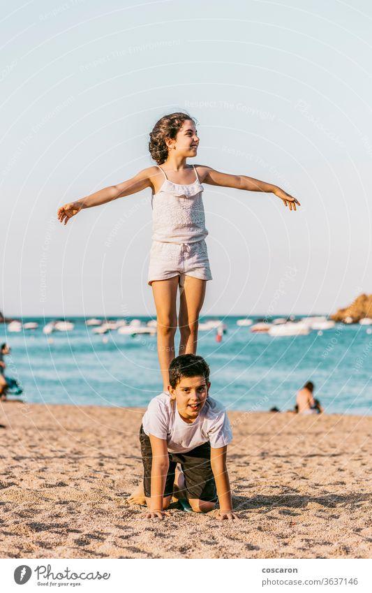 Zwei Kinder spielen am Strand Baby schön blau Bruder Kaukasier heiter Kindheit Küste Konzepte niedlich Tochter Familie Spaß Mädchen Fröhlichkeit Glück