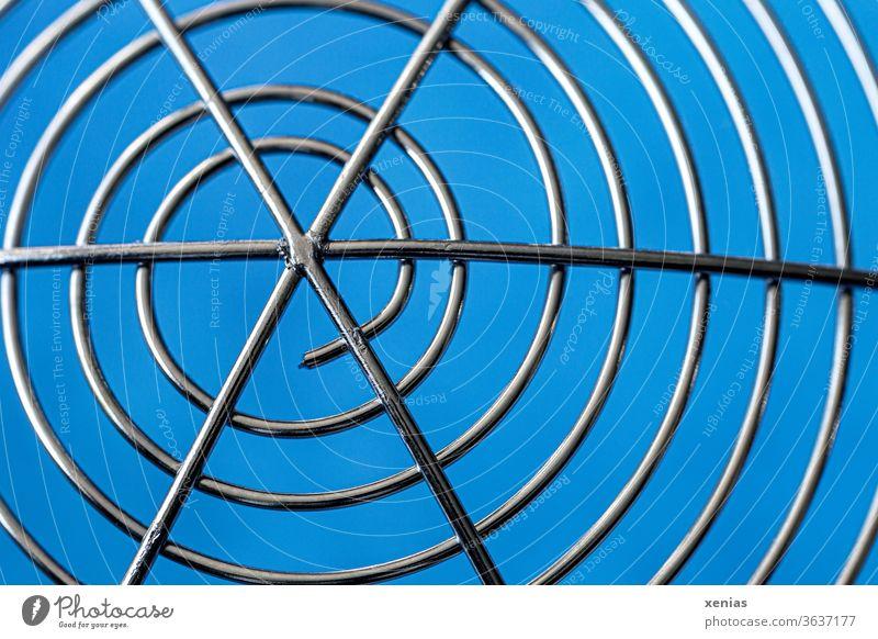 Symmetrie / Schneckenartige Windungen eines Schaumlöffels aus Edelstahl vor blauem Hintergrund Spätzleheber Nudelhelfer Rund silber Küchengeräte Detailaufnahme