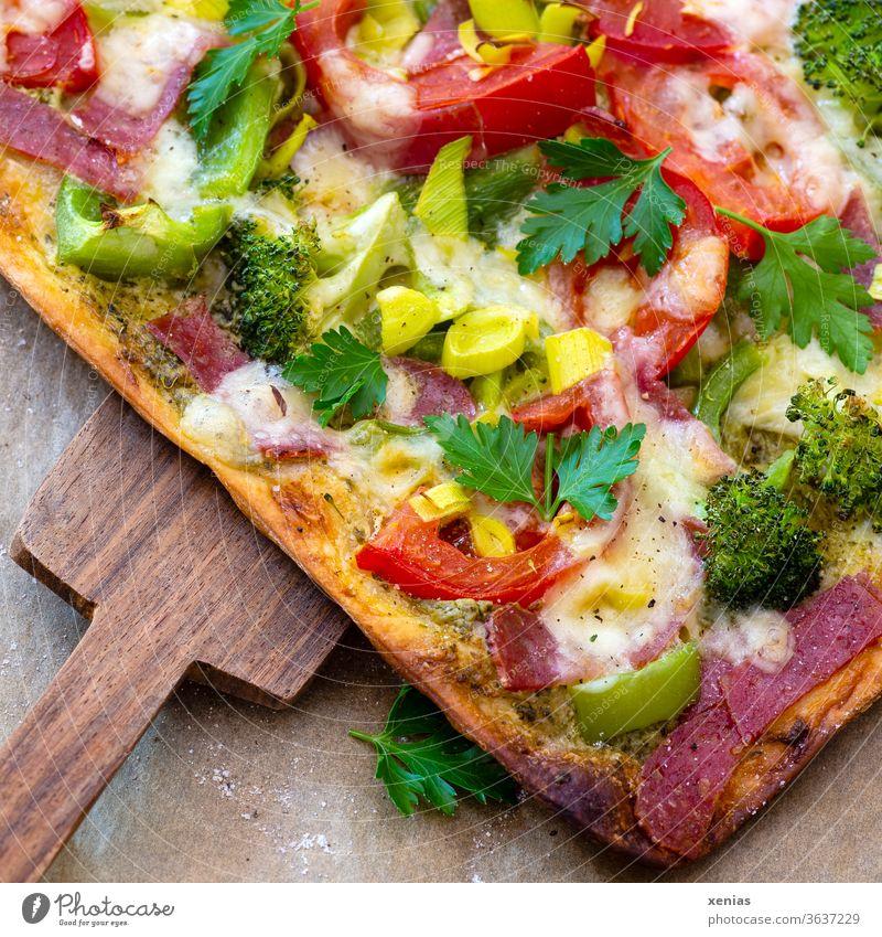 Seĺbstgebackene Pizza dick belegt mit Tomaten,  Broccoli, Lauch, Salami und natürlich viel Käse oben drauf. Das große Stück wird mit dem Holzschieber vom Backpapier geholt.