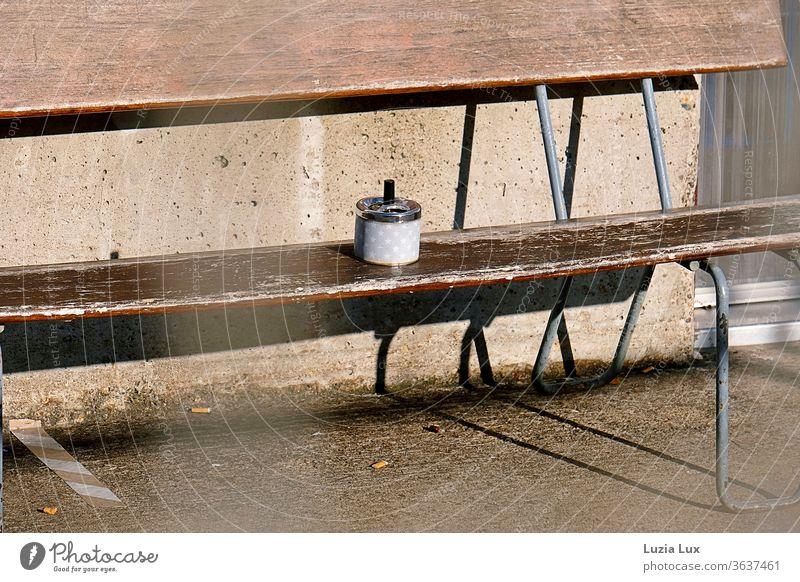Ein Raucherplatz in der Sonne: braune Holzbank, Sternchen auf dem Aschenbecher, viel Sonne und lange Schatten am Boden Sitzplatz alt sonnig Sommer Linien einsam