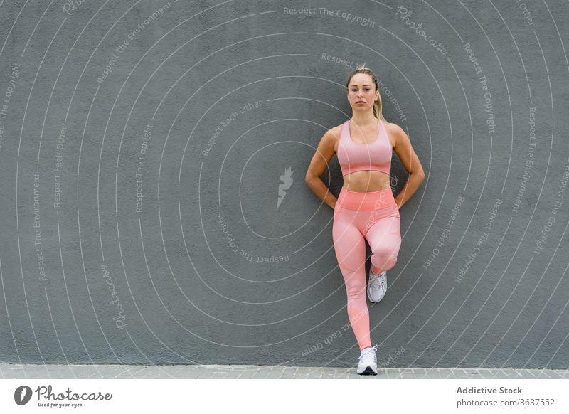 Aktiv getragene Sportlerin an graue Wand gelehnt stehend Bein anlehnen passen Gesundheit Wohlbefinden Sportkleidung Harmonie Vitalität Leggings Turnschuh