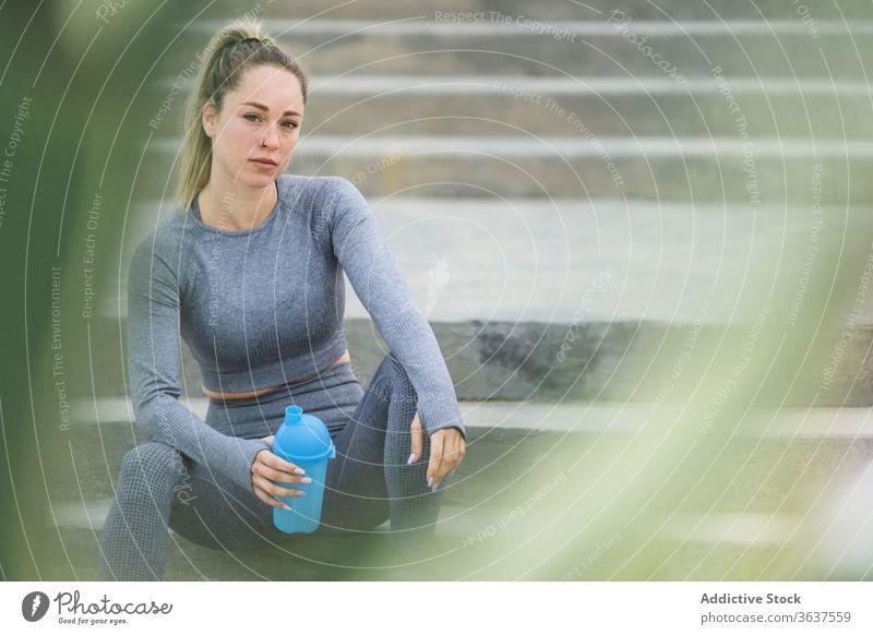 Kontemplative Sportlerin, die sich nach dem Training mit einer Flasche auf einer Treppe ausruht Athlet Pause Wasser Denken beschaulich Gesundheit ruhen