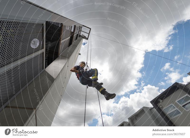 Feuerwehrmann klettert Seil gegen bewölkten Himmel herunter Training Aufstieg Gerät Mut stark Gebäude üben männlich retten komplex Uniform behüten Schutzhelm