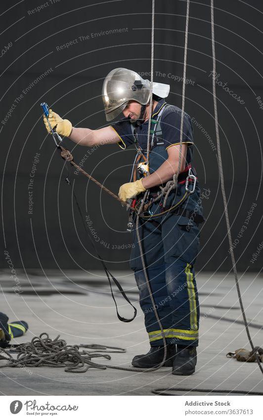 Männlicher Feuerwehrmann mit Seilen im Trainingskomplex Gerät üben Uniform behüten ausrichten männlich Mut stark retten Schutzhelm physisch aktiv professionell