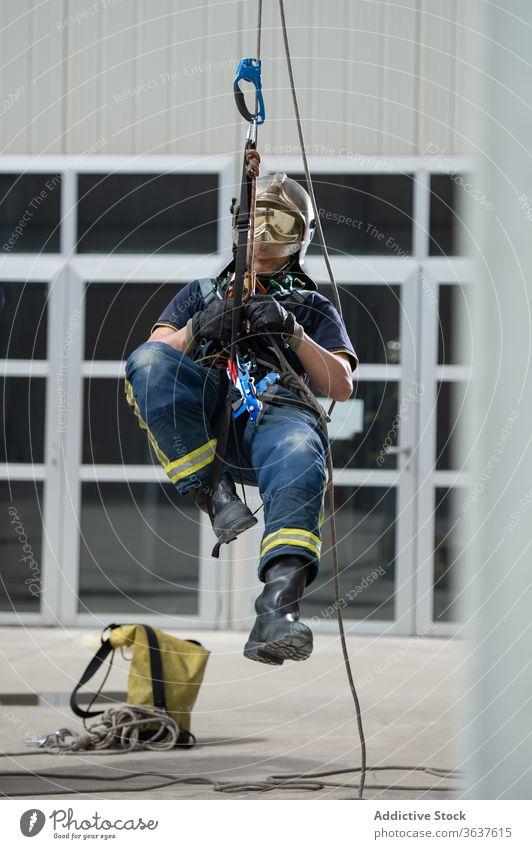 Männlicher Feuerwehrmann mit Seilen im Trainingskomplex Aufstieg Gerät Mut stark Gebäude üben männlich retten Uniform behüten Schutzhelm physisch aktiv