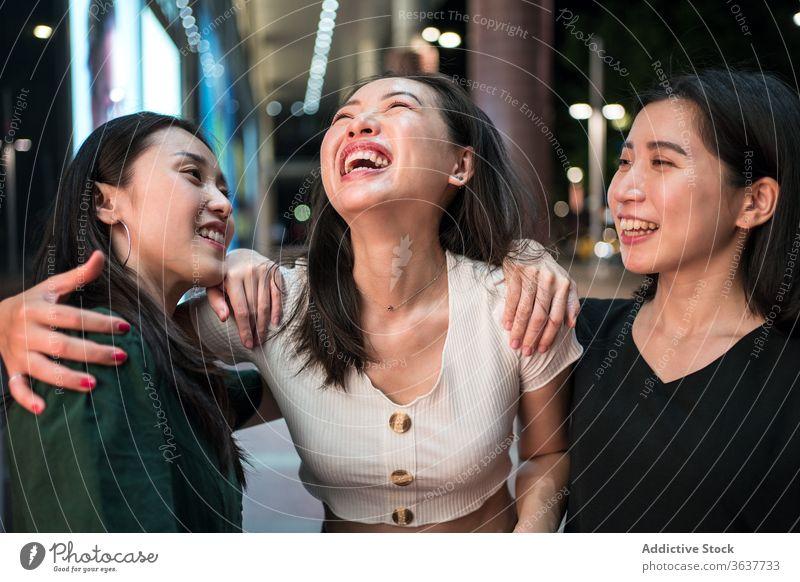 Fröhliche ethnische Frauen reden auf der Straße Unternehmen Lachen Zusammensein Freundin schlendern Großstadt Nacht heiter Humor Freundschaft asiatisch