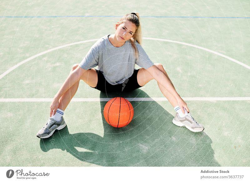 Basketballspielerin auf dem Sportplatz sitzend Frau Übung Aufwärmen Sportpark Training vorbereiten Spieler Ball Gericht Aktivität Lifestyle Wohlbefinden jung