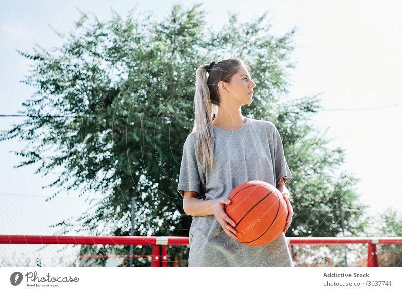 Selbstbewusster Basketballspieler auf dem Spielplatz stehend Frau selbstbewusst Sport Gericht wettbewerbsfähig ernst jung Sportlerin Ball Athlet Sportbekleidung