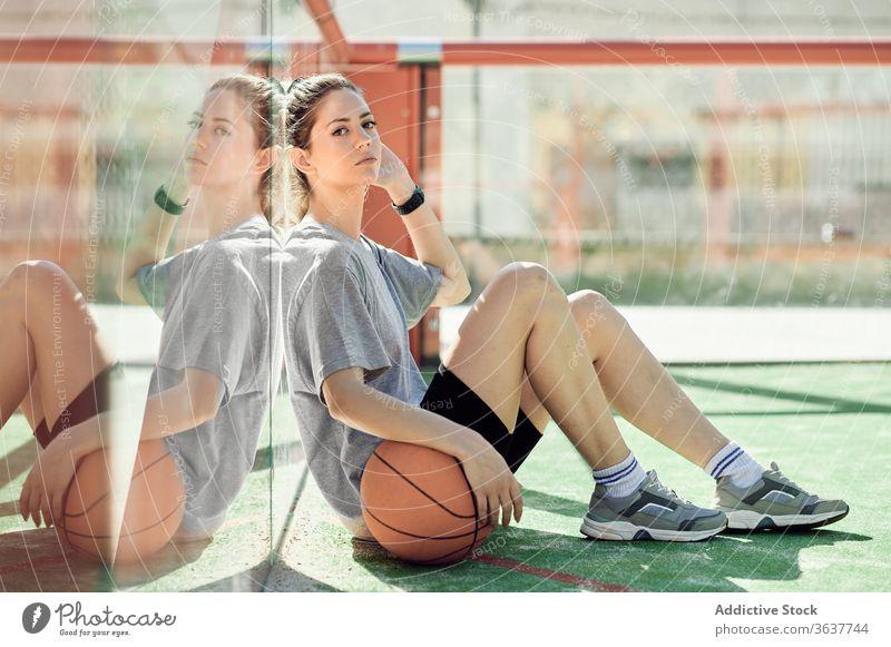 Müde Sportlerin mit auf dem Platz liegendem Basketball Frau sich[Akk] entspannen ruhen müde Gericht sitzen Ball jung Athlet Sportbekleidung Training Aktivität