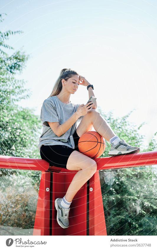 Sportlerin mit Basketball-Ball und Smartphone auf dem Spielplatz Frau benutzend Gericht ernst jung ruhen Browsen Telefon Mobile Athlet Training Aktivität