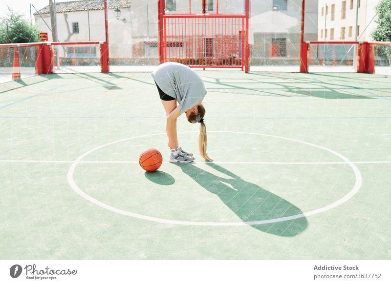Basketballspieler beim Aufwärmen auf dem Sportplatz Frau Sportpark Übung Wegbiegung Training vorbereiten Spieler Ball Gericht Dehnung Aktivität Lifestyle
