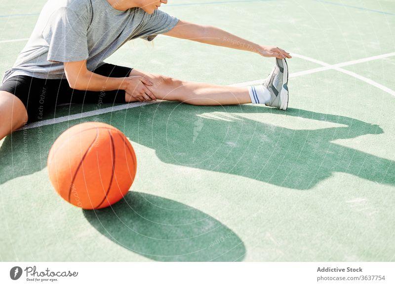 Basketballspielerin beim Stretching auf dem Sportplatz Frau Dehnung Übung Aufwärmen Sportpark Training vorbereiten Spieler Ball Gericht Aktivität Lifestyle
