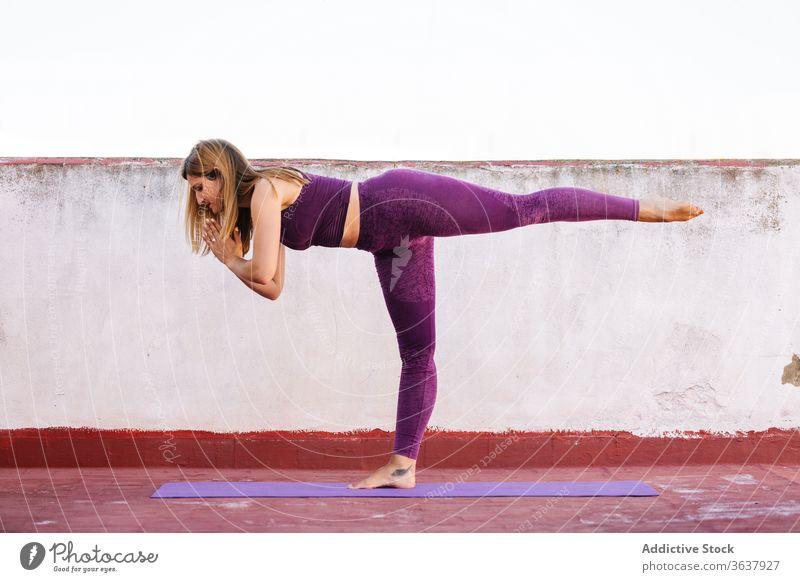 Ruhige, Yoga praktizierende Frau in Kriegerposition Krieger-Pose üben Gleichgewicht Namaste gestikulieren Gesundheit Unterlage Terrasse Harmonie Asana