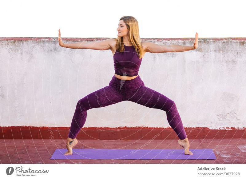 Zufriedene Frau, die während des Trainings plie hockt Kniebeuge Terrasse passen auf Zehenspitzen Übung Sportkleidung Gesundheit Unterlage Fitness Athlet