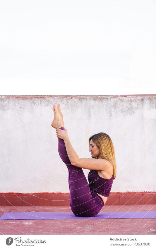 Flexible Frau praktiziert Yoga in einer Boot-Asana üben Boot-Pose navasana Gleichgewicht Achtsamkeit Unterlage sich[Akk] entspannen beweglich Windstille