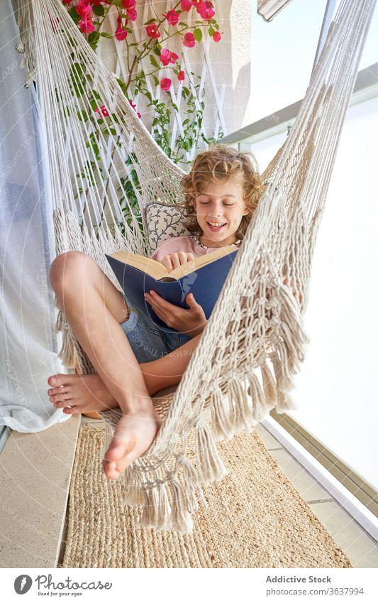 Junge sitzt in Hängematte und liest zu Hause Buch lernen Bildung Wissen intelligent lesen fokussiert Glück Kindheit Komfort Lächeln besinnlich Harmonie lässig