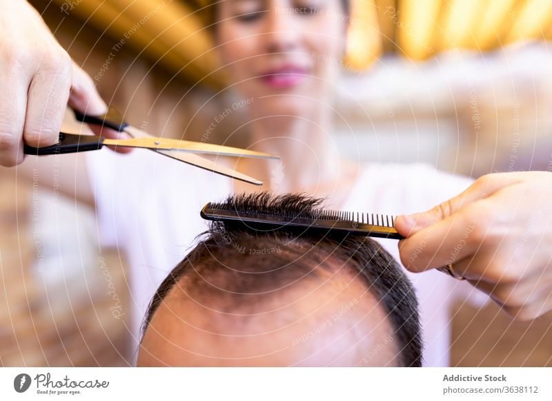 Friseurin schneidet Haare, um unkenntlich zu werden Mann in Friseursalon entgittern Klient Behaarung Schere geschnitten Kamm Haarschnitt Meister Barbershop
