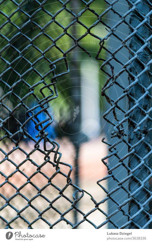 Loch in einem Maschendrahtzaun durch geschnitten gefährlich stechend Beschädigte Begrenzung Stahl verdrahtet Muster mit Stacheln versehen Industrie Schutz Käfig