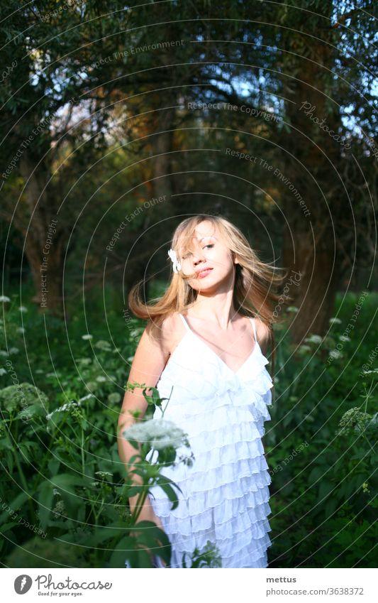 Blondhaarige Dame, die in einem weißen Sommerkleid mit windgewelltem Haar in den Wäldern tanzt. Emotionales und natürliches Bild mit Copyspace. Tanzende Dame
